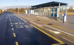 view of a bus shelter with yellow marking on floor saying bus stop.