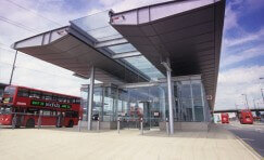 front of a bus station with a large covered canopy either side of the bus station.