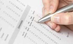 close up view of a hand with a pen filling out a questionnaire.