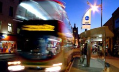view of an installed bus shelter with a blurred bus leaving the bus stop.