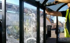 view of a Trueform employee replacing damaged glazed screens on a bus shelter.