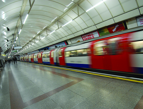 view of a train whizzing past in an underground station.