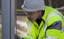 view of Trueform employee performing maintenace on bus shelter.