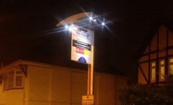 view of an installed elite solar bus stop sign at night.
