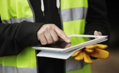 view of Trueform employee in a hi-vis jacket using a tablet.