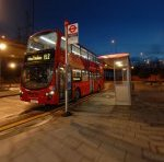 London bus stop sign and bus shelter with a double decker bus at the stop.