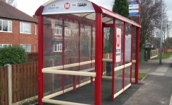 Metro bus shelter with public seating inside.